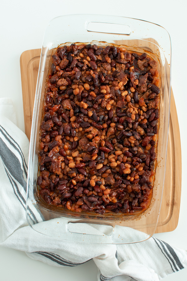 Baked beans with ground beef and bacon in a casserole dish.