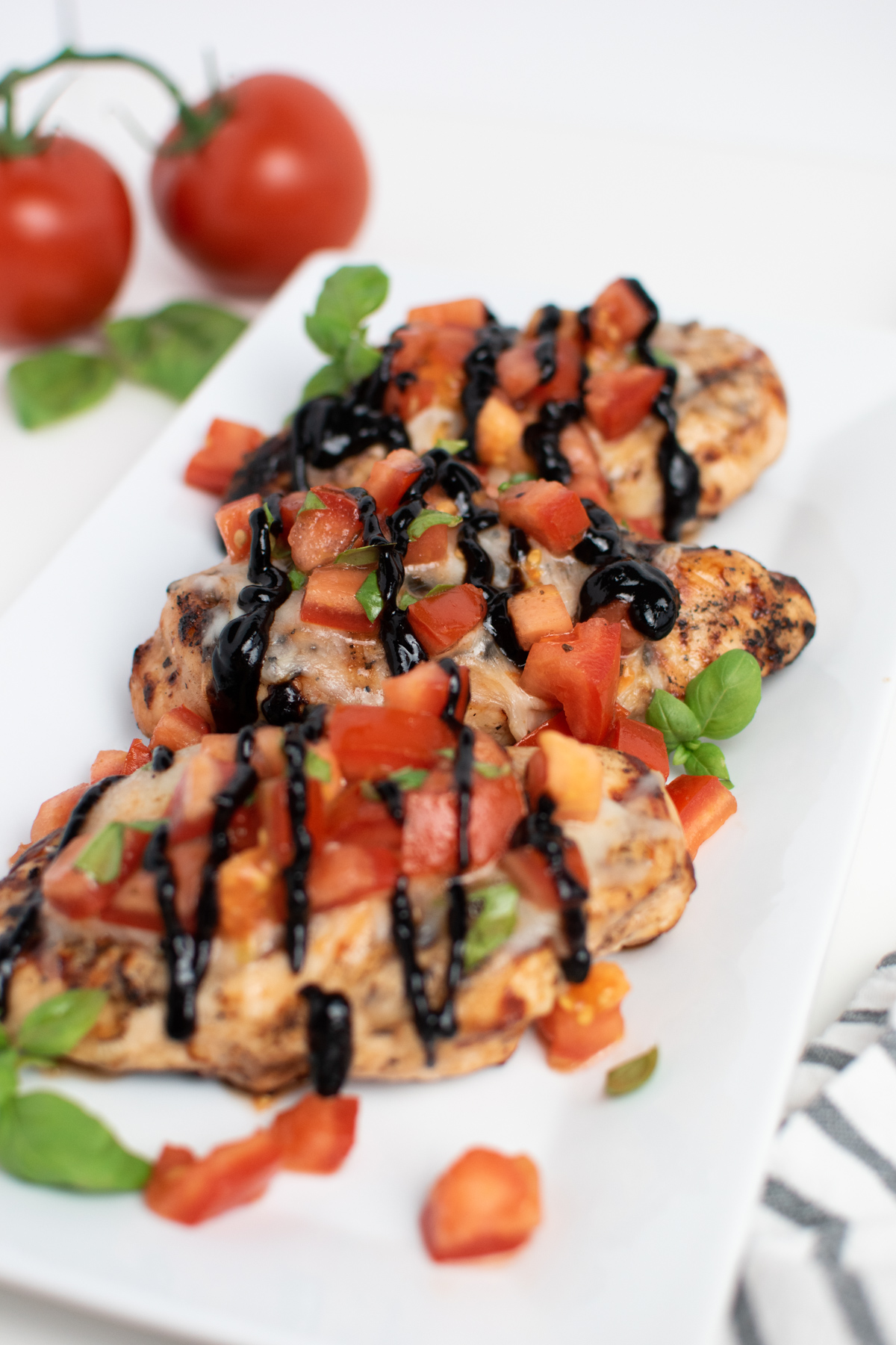 Three pieces of grilled bruschetta chicken on white platter with fresh tomatoes in background.