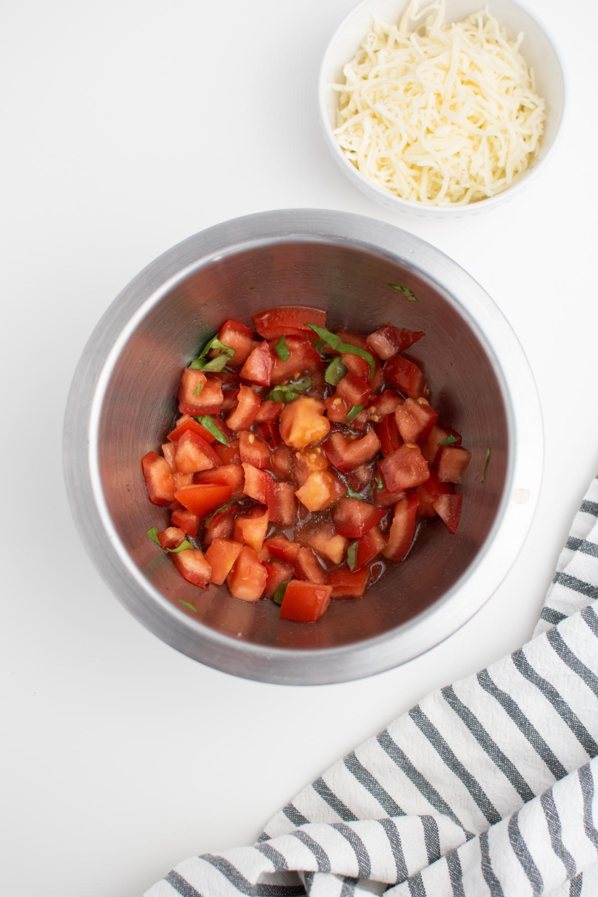 Fresh bruschetta in small bowl on white table.
