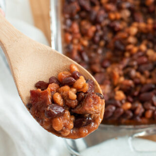 Calico baked beans on a wooden spoon.