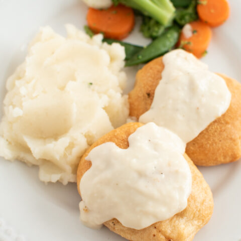 Chicken pillows with gravy on a dinner plate.