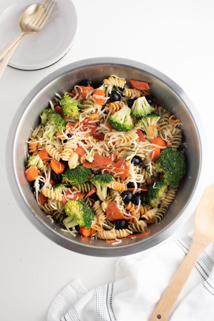 Large bowl of Italian pasta salad on white table.