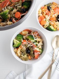 Tri color pasta salad recipe in white bowls.