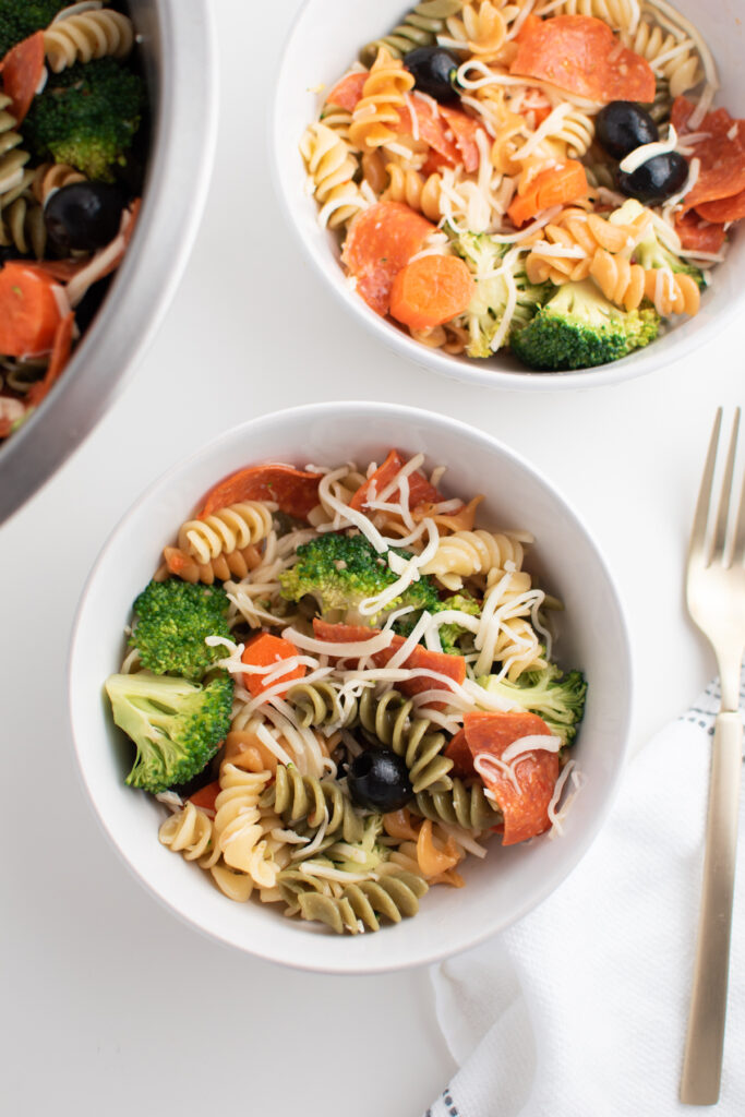 Tri color pasta salad with Italian dressing in white bowls.