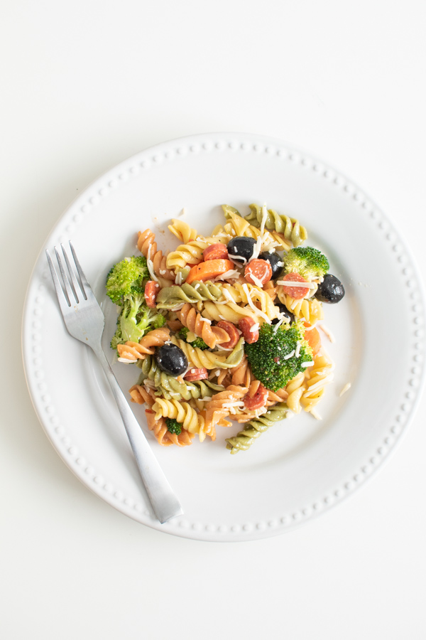 Tri color pasta salad with Italian dressing on a plate.