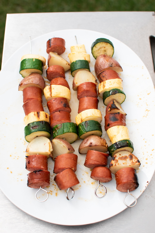 Grilled sausage kabobs on a white platter.