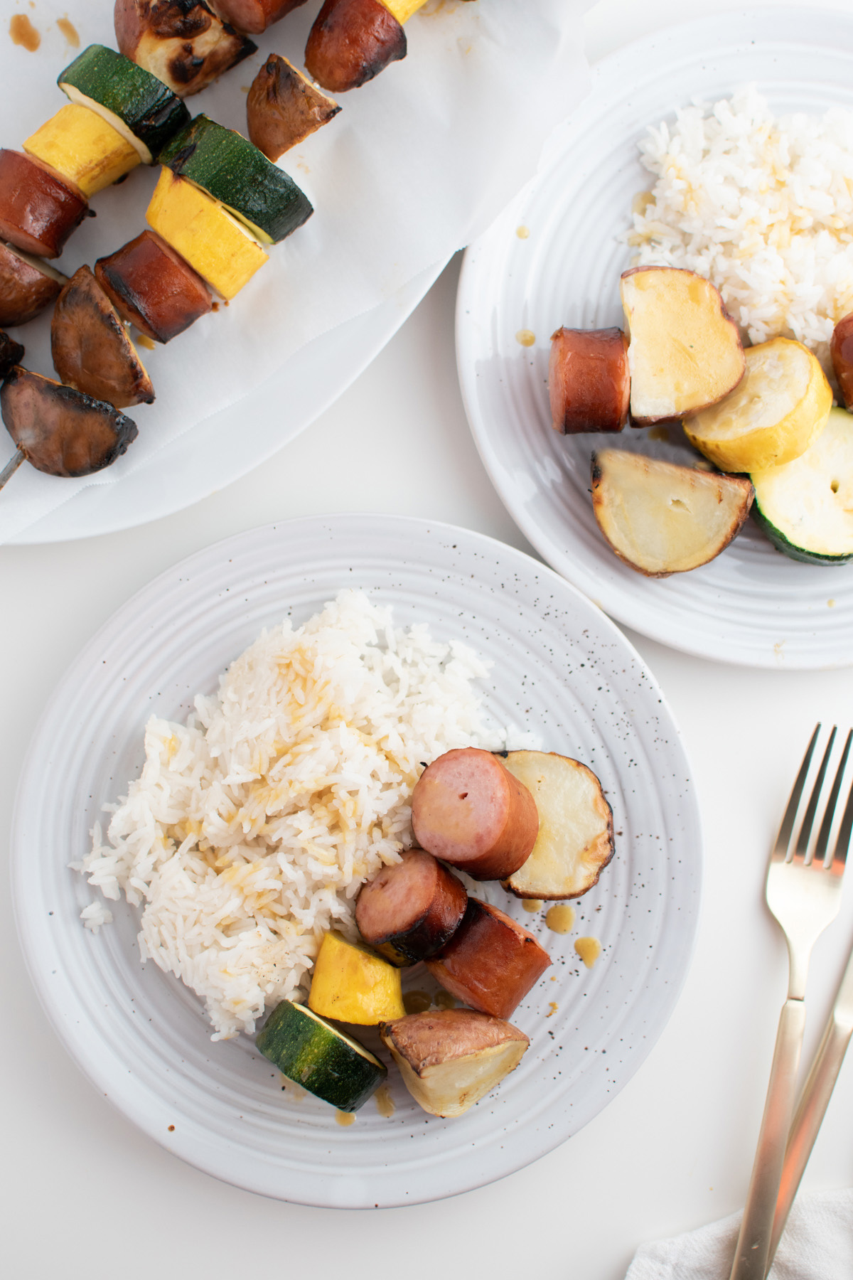 Two plates of grilled sausage, potatoes, squash, and rice on white table next to gold utensils.