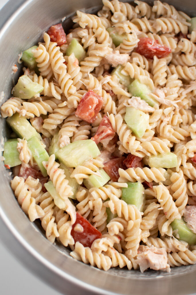 Rotini pasta salad with Italian dressing in large bowl.