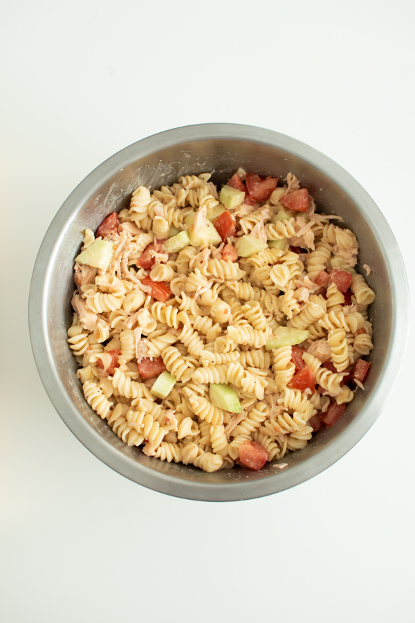 Rotini pasta salad in a mixing bowl.