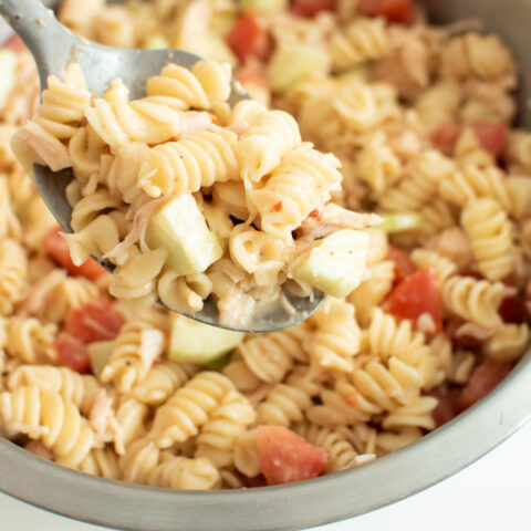Rotini pasta salad with Italian dressing on a serving spoon.