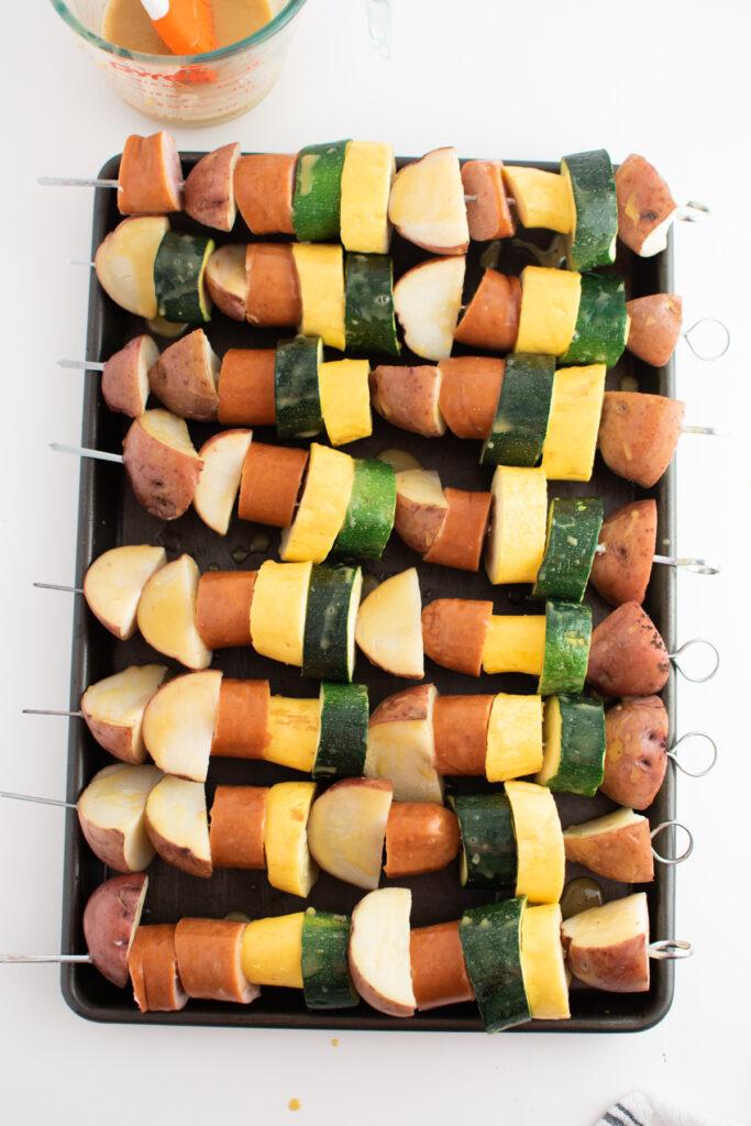 Sausage and potato kabobs on baking sheet.