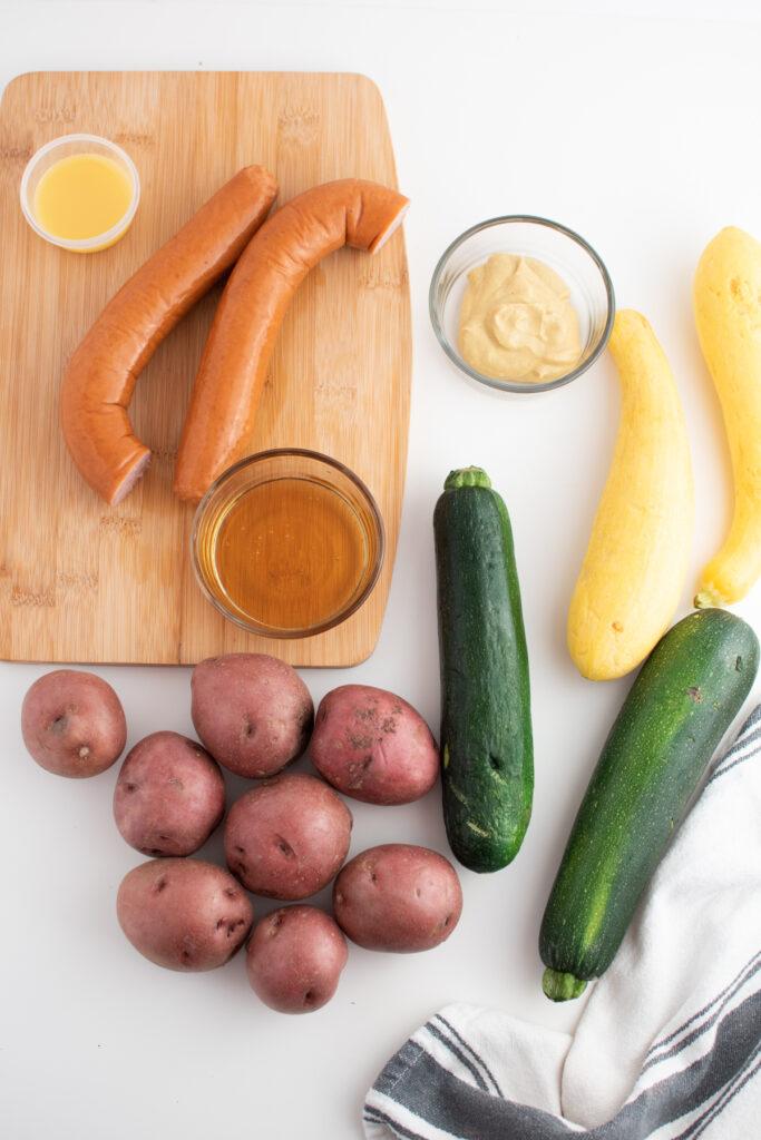 Sausage kabob ingredients on white table.