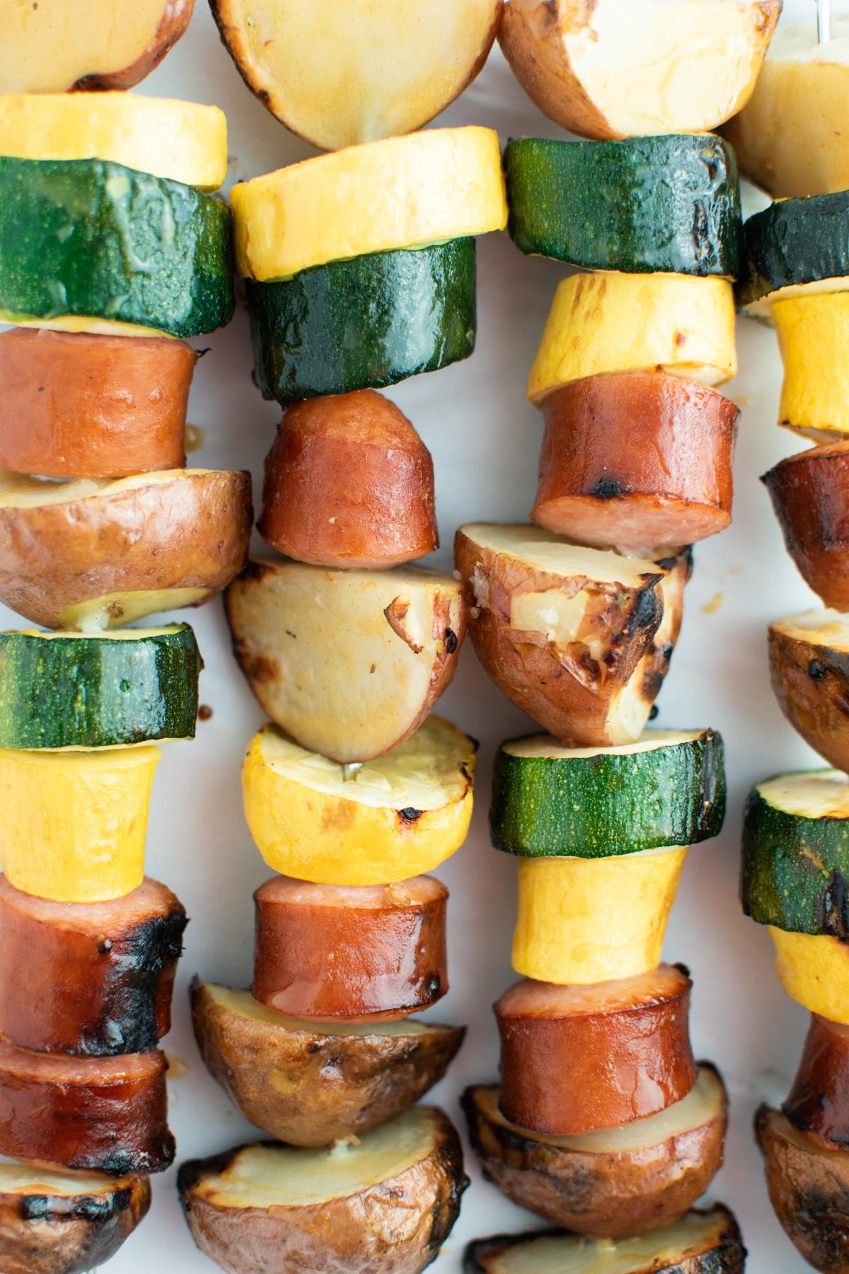 Close up of sausage, potato, and squash kabobs with honey glaze.