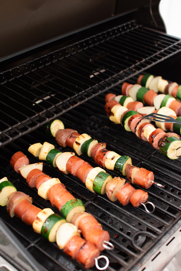 Sausage kabobs with potatoes and squash on a grill grate.