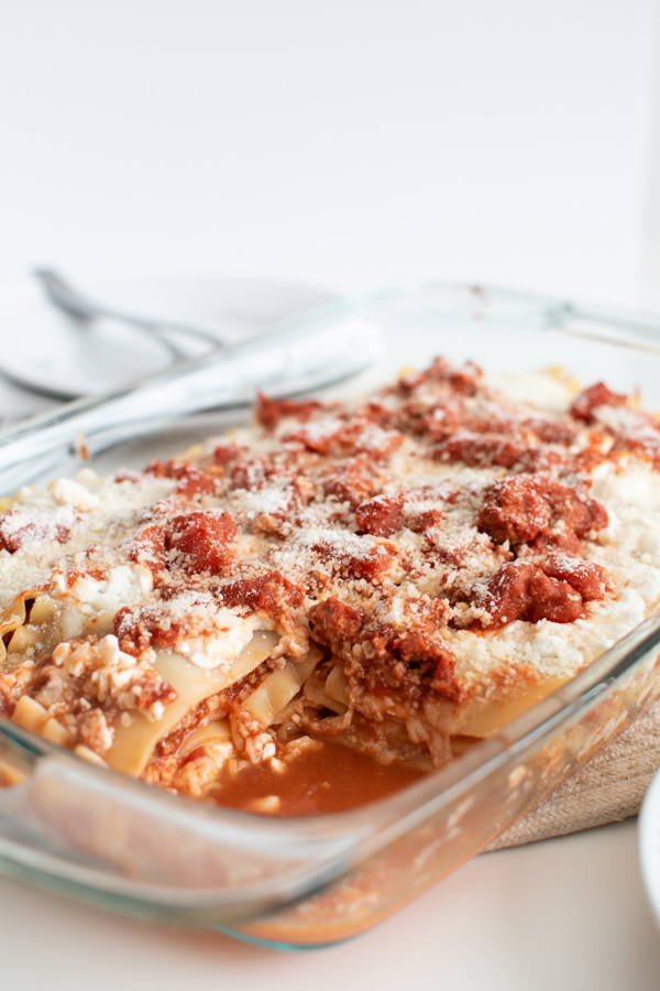 Full pan of lasagna using cottage cheese with a corner piece removed.