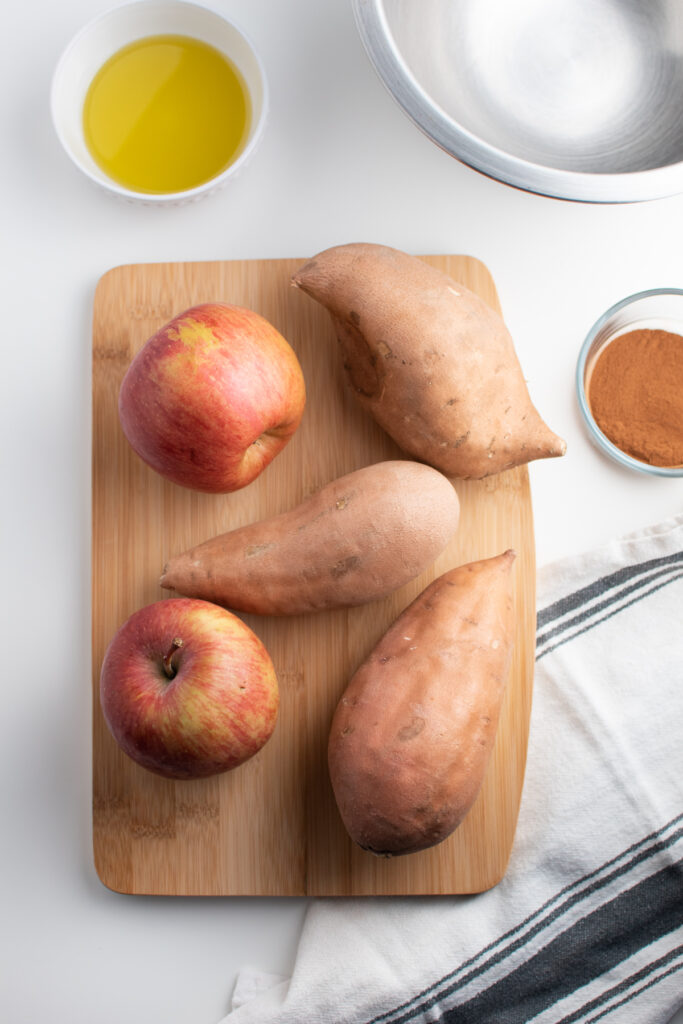 Raw aplles and sweet potatoes on a cutting board.
