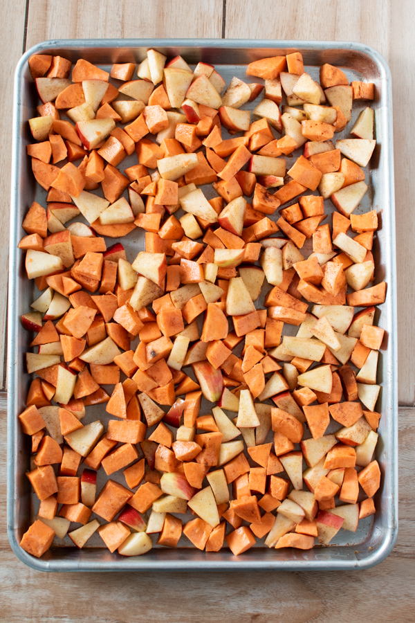 Chopped sweet potatoes and apples on a sheet pan.