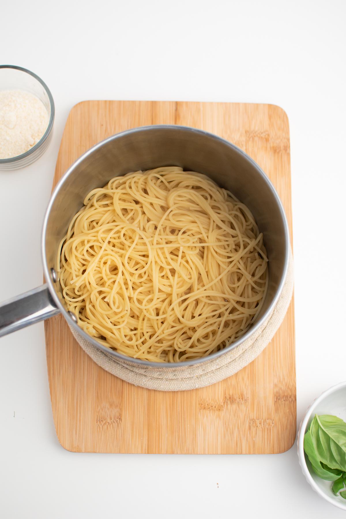 Cooked thin spaghetti in pot on wood cutting board.