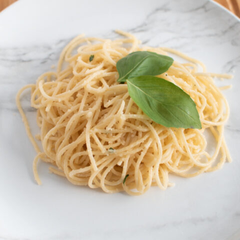 Lemon and basil pasta on a marble plate.