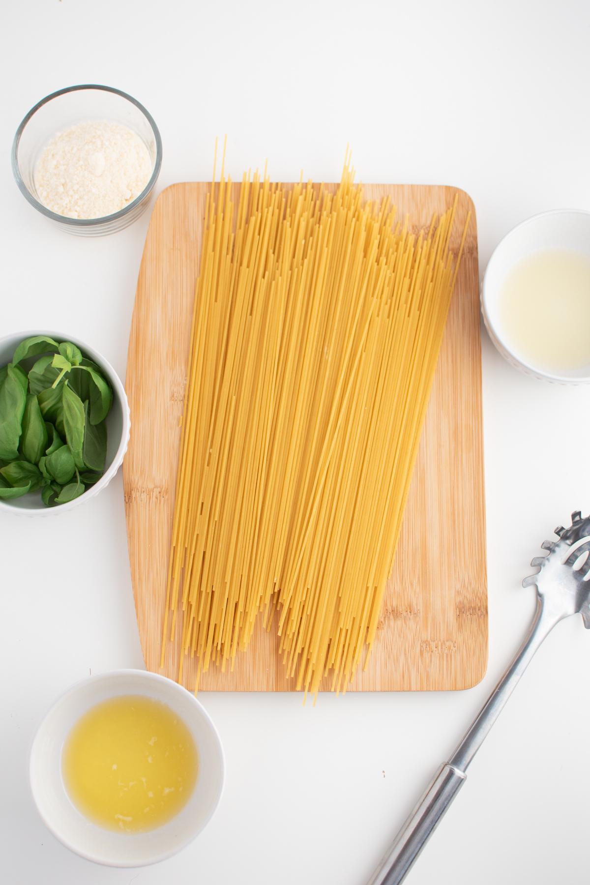 Bowls of lemon basil pasta ingredients on white table.