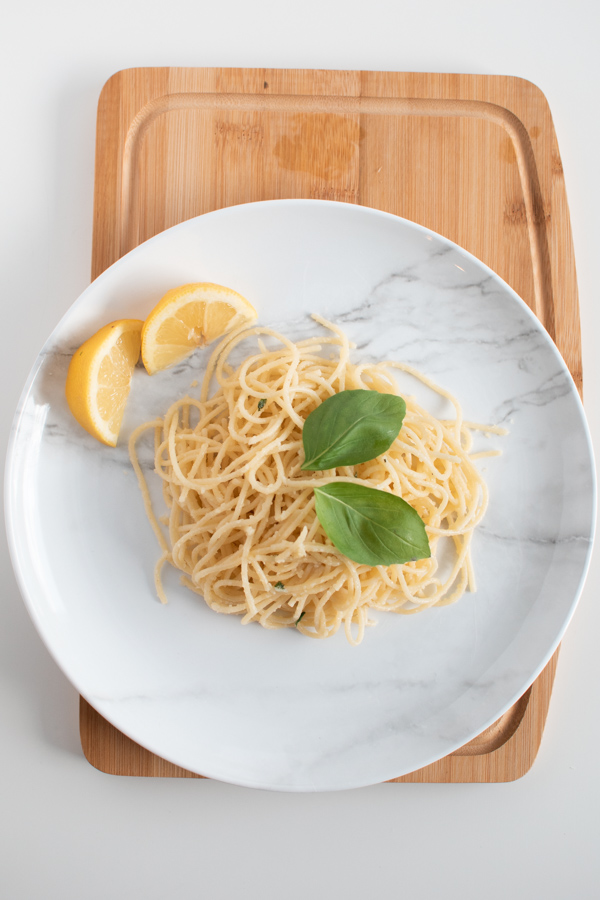 Lemon parmesan pasta on a marble plate and cutting board.