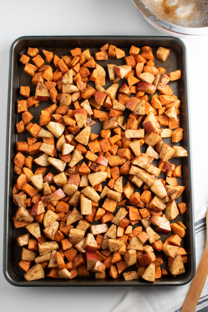 Roasted sweet potatoes and apples on a sheet pan.