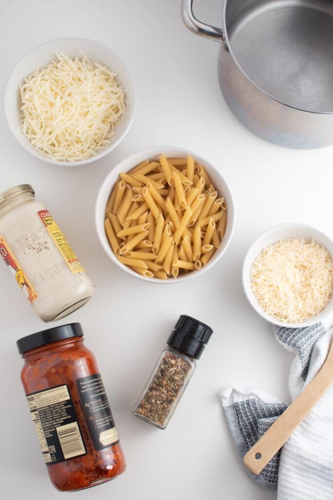 Pasta bake ingredients on white table.