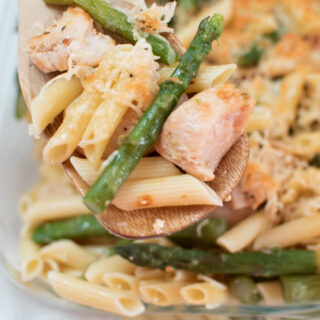 Penne with chicken and asparagus on a wooden spoon.