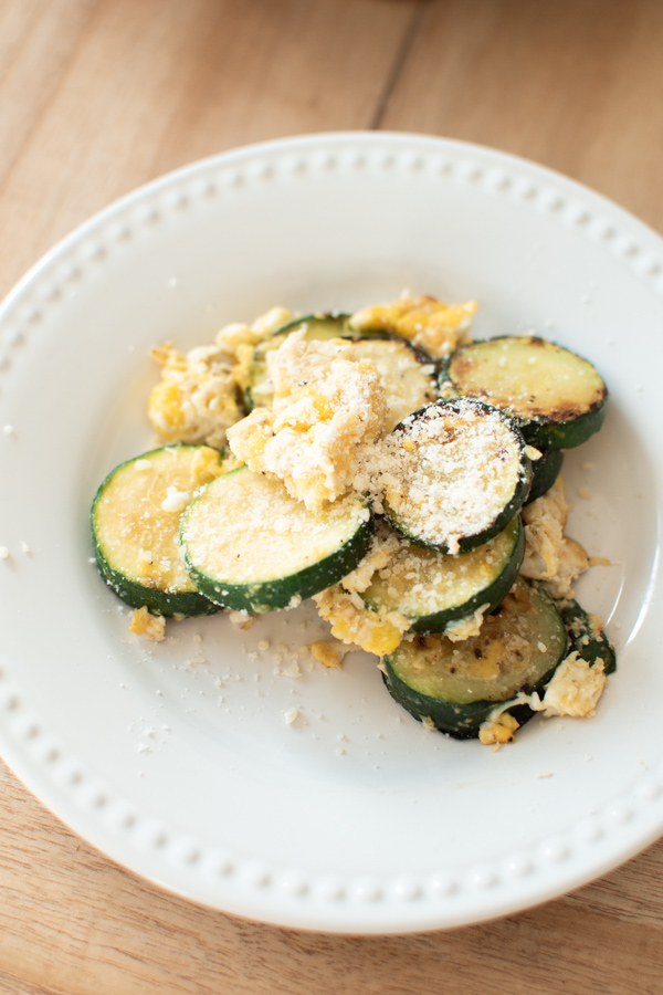 Zucchini and eggs on a white plate.