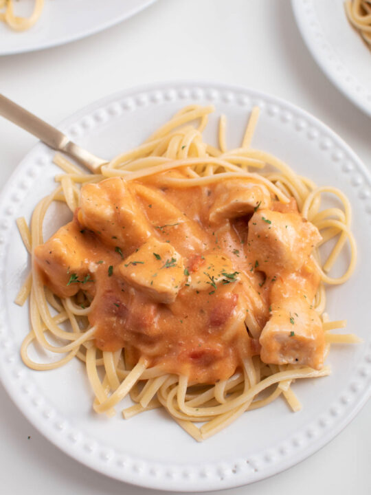 Linguine topped with cheesy chicken sauce on white plate with gold fork in it.