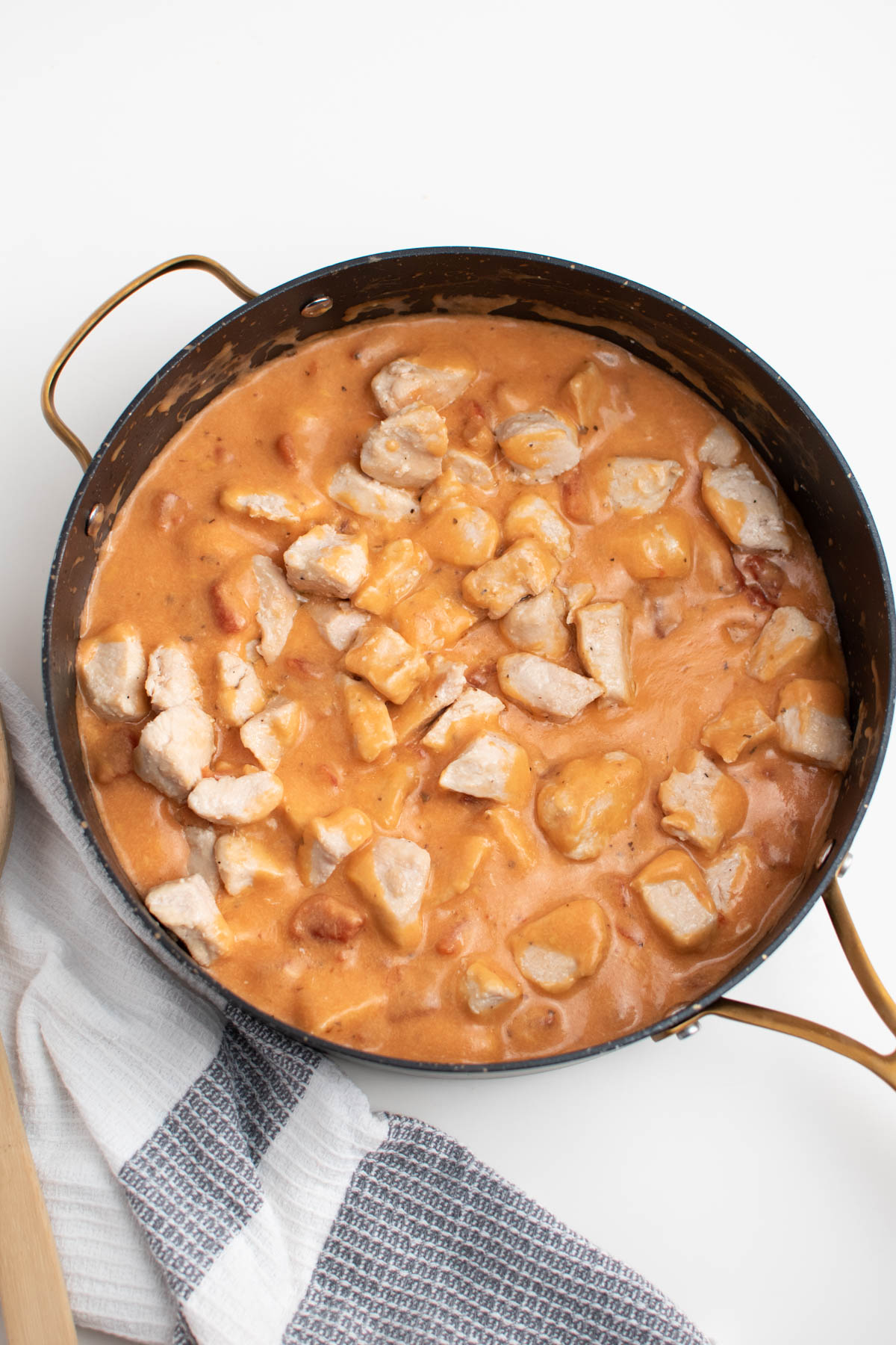 Cooked chicken cubes and cheesy tomato sauce in large skillet.
