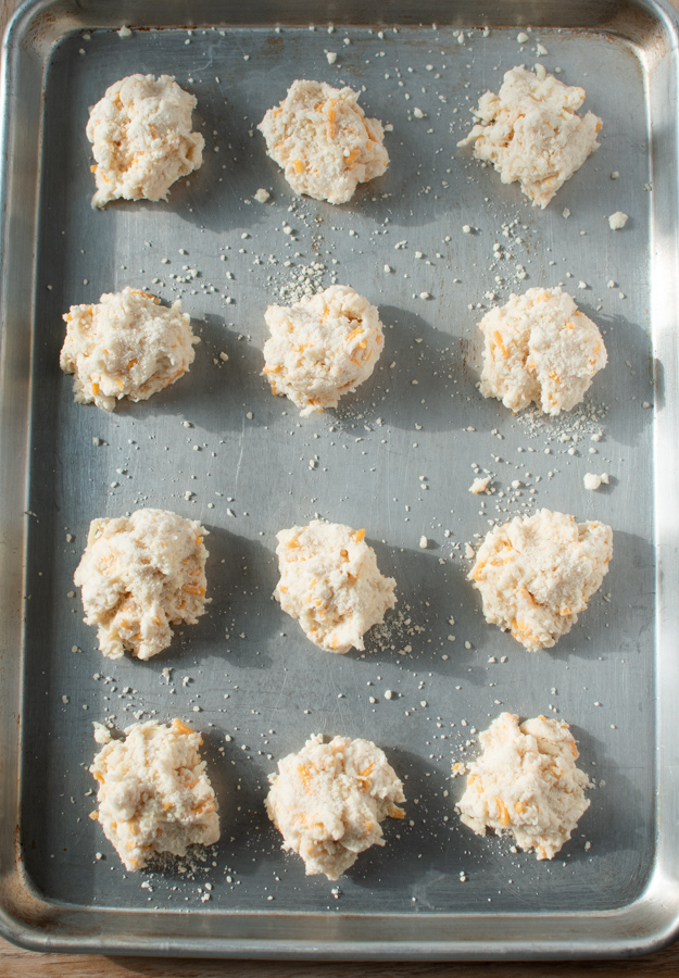 Cheddar cheese biscuits on a sheet pan.