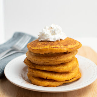 Pumpkin pancakes with pancake mix stacked on a plate.
