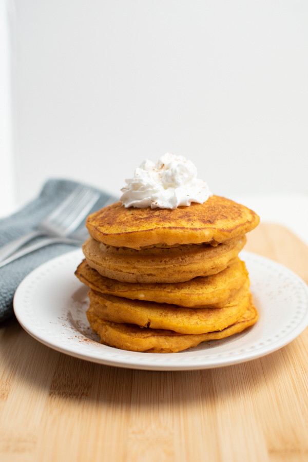 Five pumpkin pancakes made with pancake mix stacked on white plate with whipped cream on top.