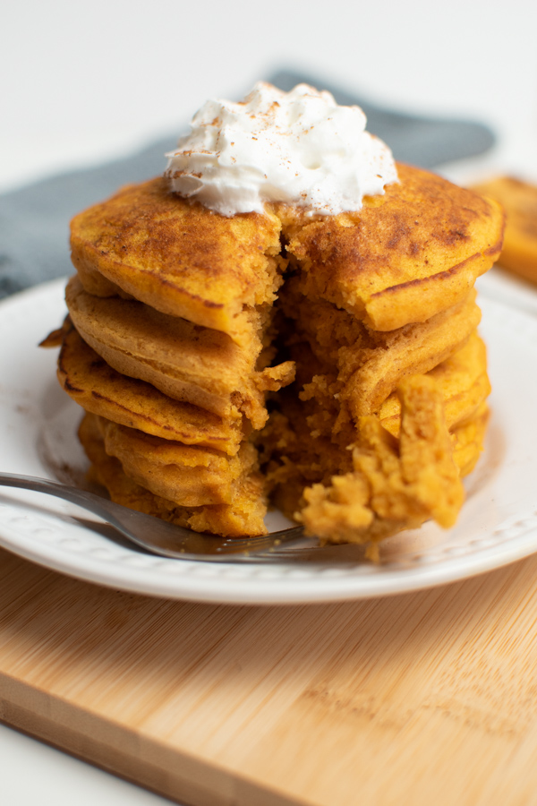 Fork with pancake on it in front of pumpkin spice pancake stack with a slice taken out.