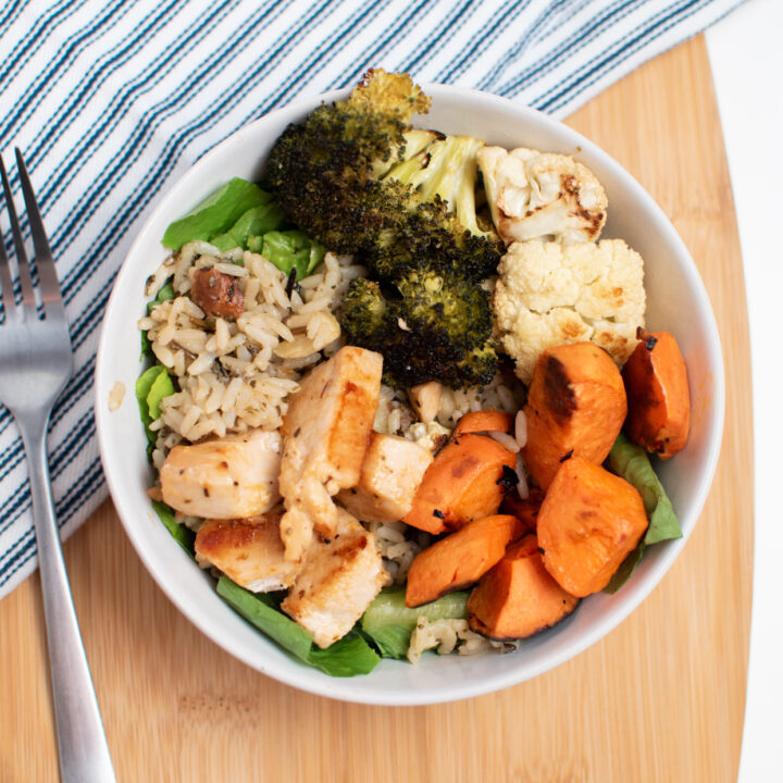 A chicken buddha bowl with sweet potatoes and vegetables on a cutting board.