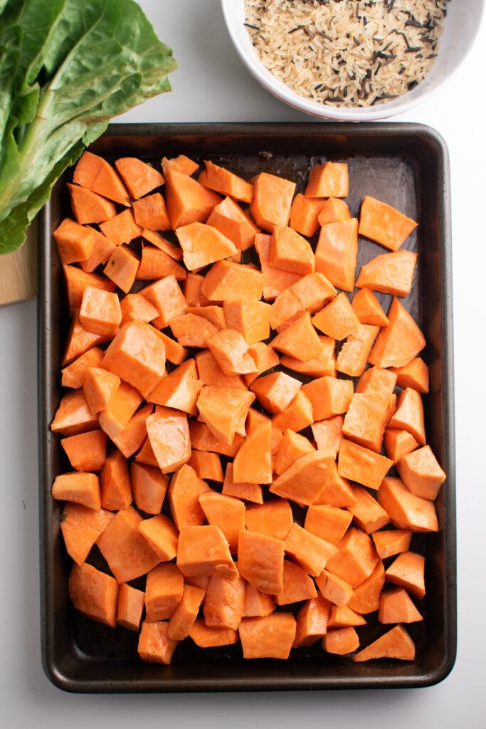 Cubed sweet potato pieces on sheet pan.