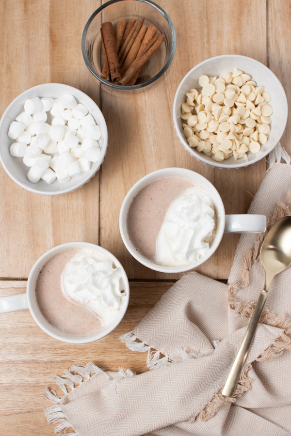 Two mugs of homemade white hot chocolate next to bowls of marshmallows, cinnamon sticks, and white chocolate chips.