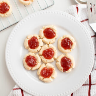Jam filled cookies on a white plate.