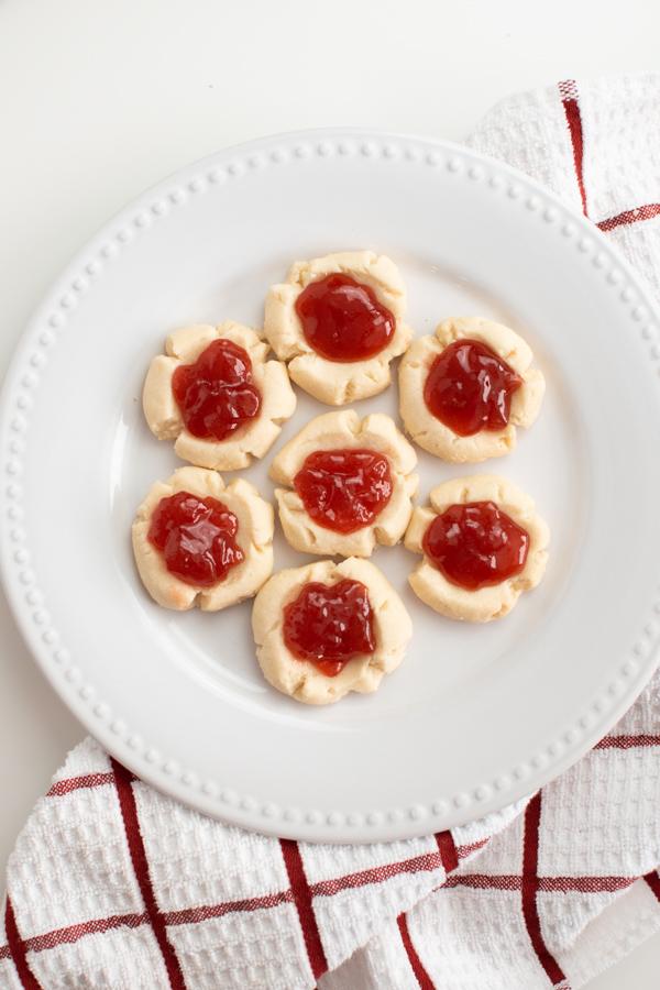 Jam thumbprint cookies on a white plate.