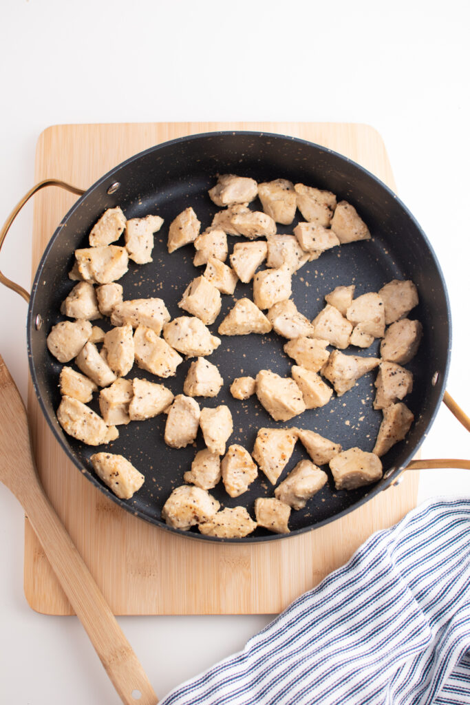 Lemon pepper chicken pieces in skillet.