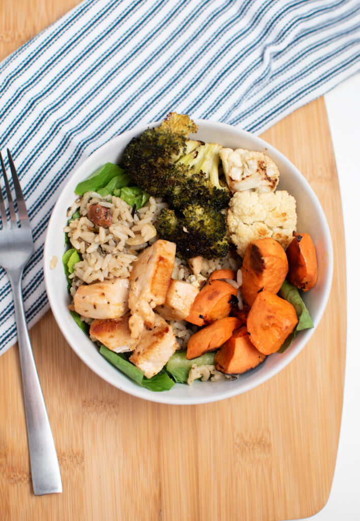 A power bowl with chicken and roasted vegetables on a cutting board.