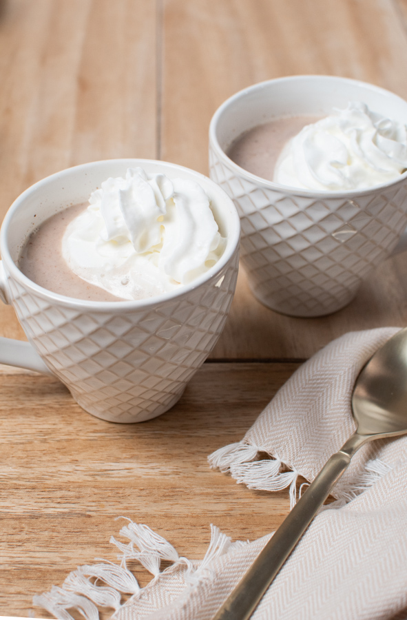 Two white mugs filled with white hot chocolate and whipped cream on wood table.