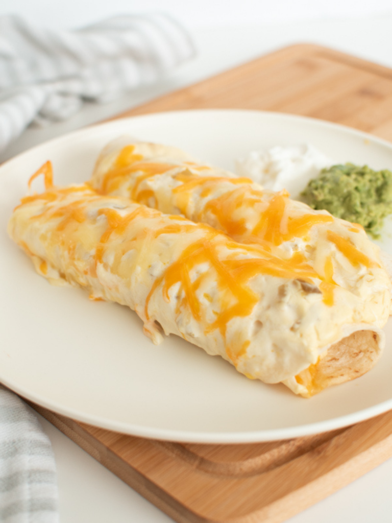Chicken enchiladas with sour cream white sauce on a plate.