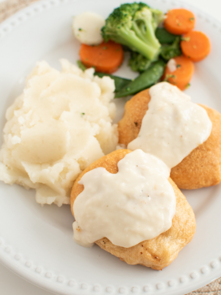 Chicken pillows with gravy on a white plate.