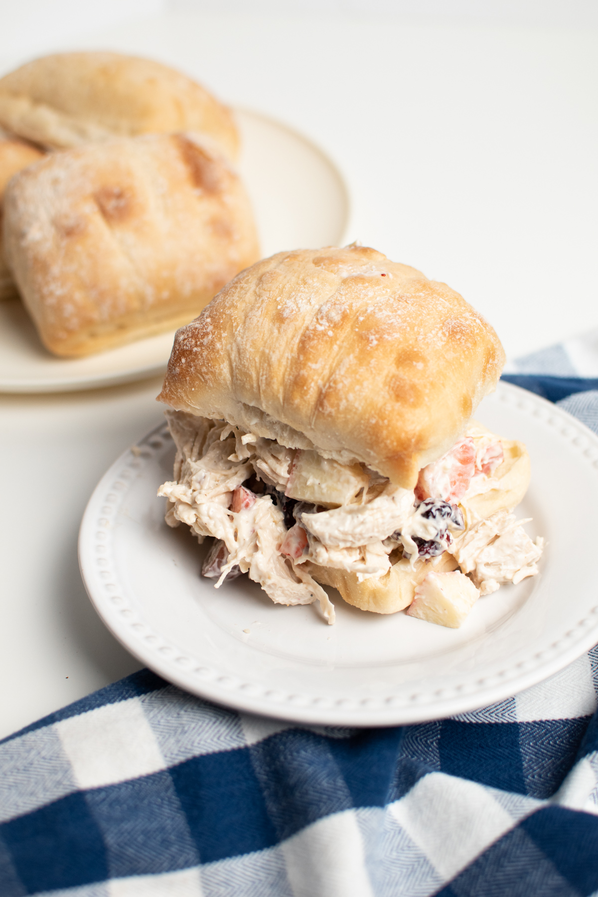 Chicken salad with apples, strawberries, and grapes on ciabatta roll on a white plate.