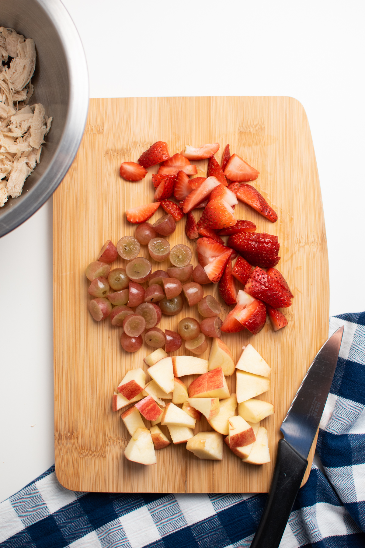Chopped strawberries, grapes, and apples on wood cutting board next to knife and bowl with chicken.