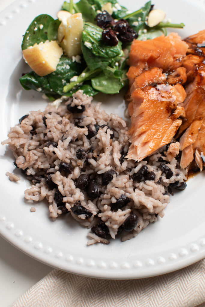 Coconut milk rice and black beans on a dinner plate.
