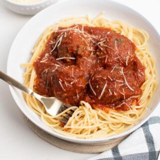 Italian spaghetti and meatballs in a white dish.