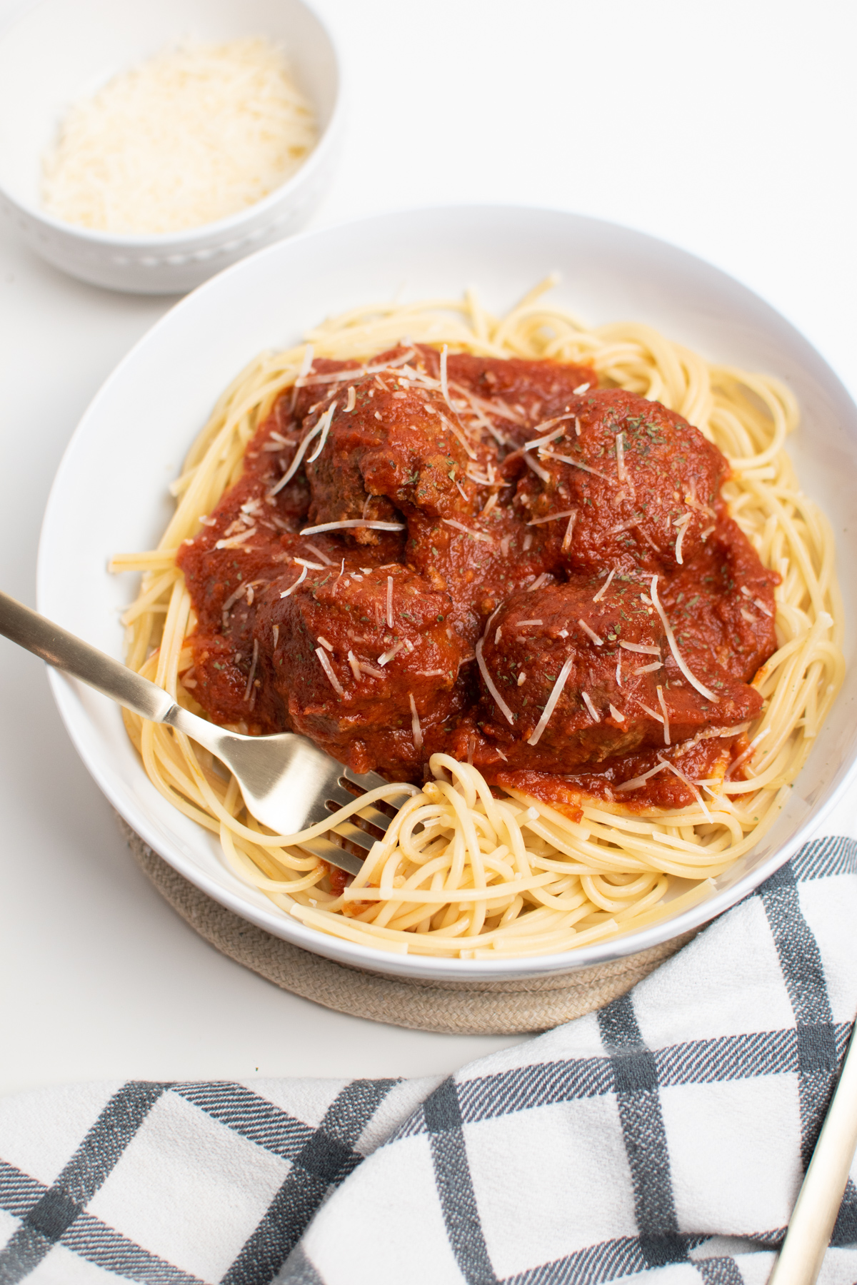 Fork in bowl with Italian spaghetti and meatballs on white table.